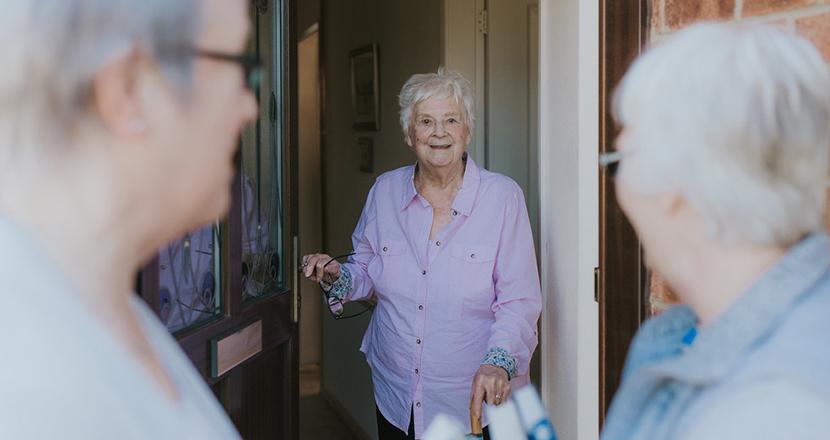 An older woman at her front door