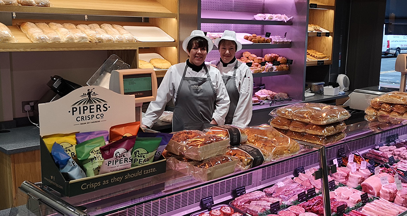 A photography of staff standing next to the meat counter in Birketts