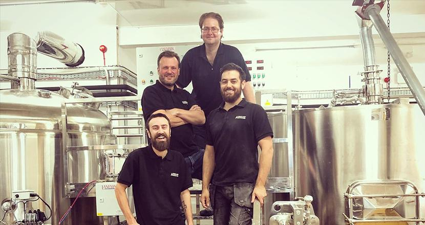 A photograph of 4 men next to a distillery